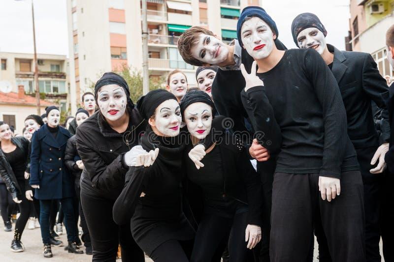 Die Jungen und Mädchen, die als Pantomimen maskiert werden, nehmen an der Maskerade teil lizenzfreies stockbild