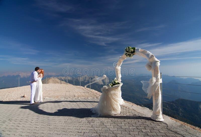 Die Jungvermähltenumarmungen nähern sich dem Hochzeitsbogen lizenzfreies stockfoto