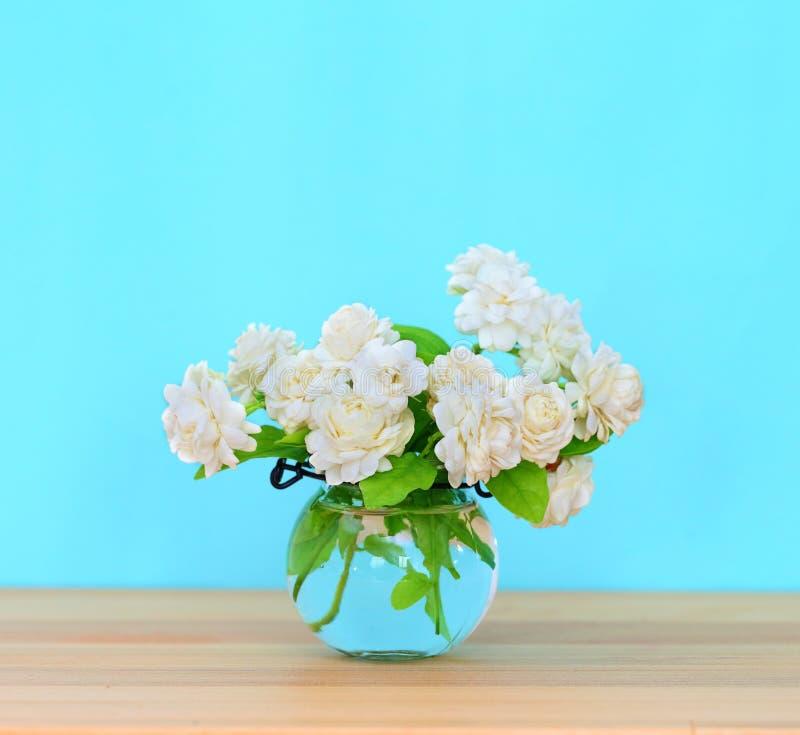 Die künstliche Jasminblume im Topf am hölzernen Tisch mit stockbild