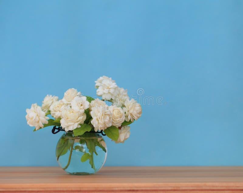 Die künstliche Jasminblume im Topf am hölzernen Tisch mit stockfoto