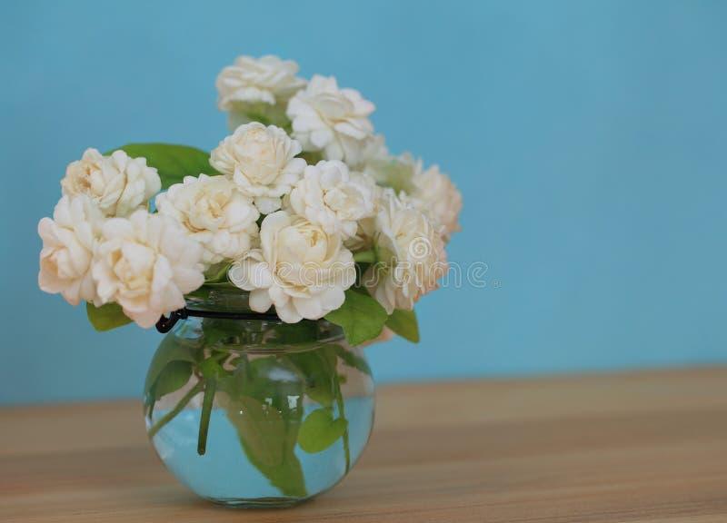 Die künstliche Jasminblume im Topf am hölzernen Tisch mit lizenzfreies stockbild