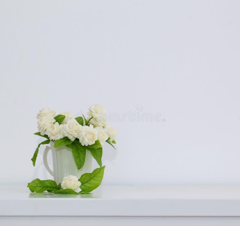 Die künstliche Jasminblume im Topf am weißen Tisch mit stockbilder