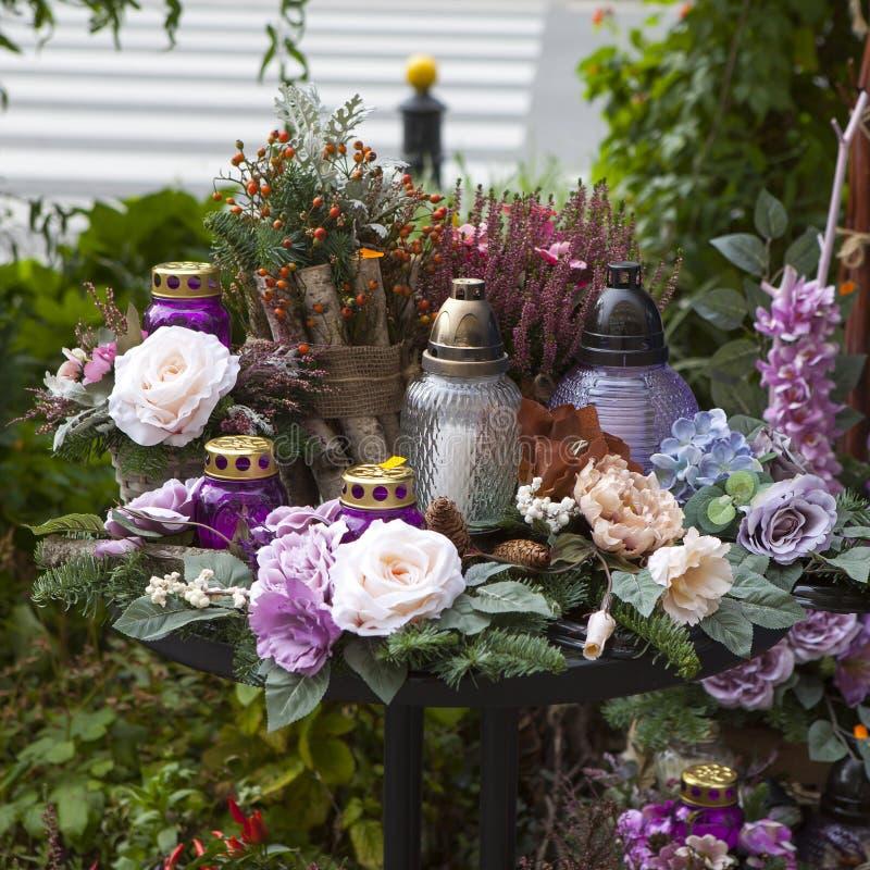 Die künstlichen und vibrierenden Blumen, Kerzen in den purpurroten Tönen bis zum dem Tag der Toten in Warschau lizenzfreie stockfotografie