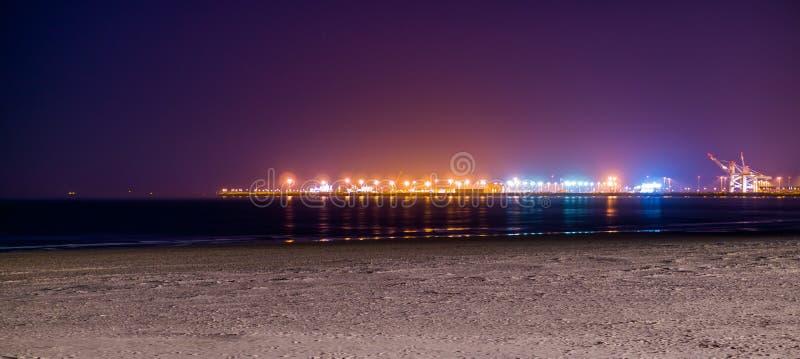 Die Küstenlinie von Blankenberge-Strand beleuchtet bis zum Nacht, bunte Lichter auf dem Industriegelände im Abstand lizenzfreies stockfoto