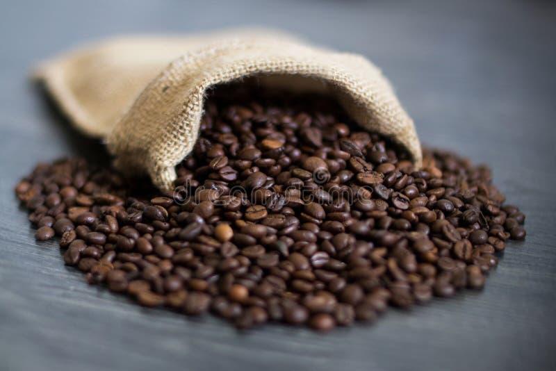 Die Kaffeebohnen, die heraus aus einer Tasche gießen lizenzfreie stockfotos