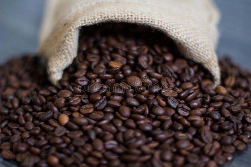 Die Kaffeebohnen, die heraus aus einer Tasche gießen lizenzfreie stockbilder