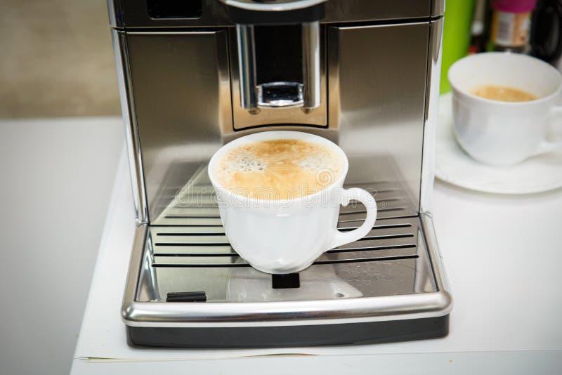 Die Kaffeemaschine gießt frisch gebrauten Kaffee in eine weiße Schale Kaffee mit Schaumgummi lizenzfreie stockbilder