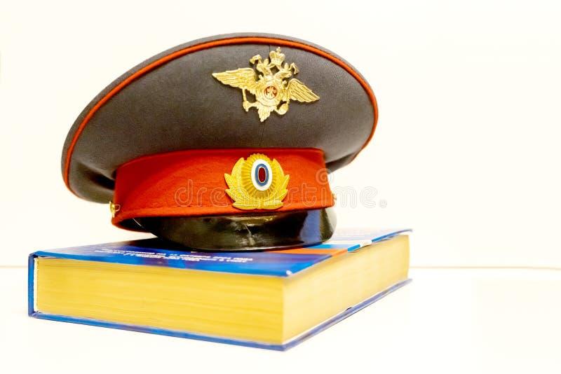 Die Kappe eines russischen Polizeibeamten ist auf dem Code von Gesetzen isolat lizenzfreies stockbild