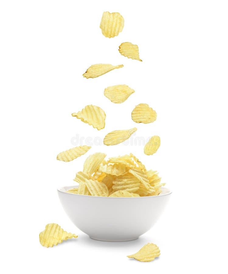 Die Kartoffelchips, die in das Fayenceweiß fallen, rollen Lokalisiert auf Whit stockfotografie