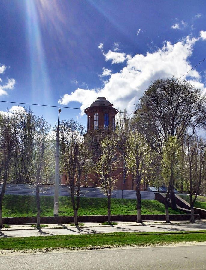 Die katholische Kirche, der blaue Himmel, hinter den grünen Bäumen, in der Sonne stockfotografie