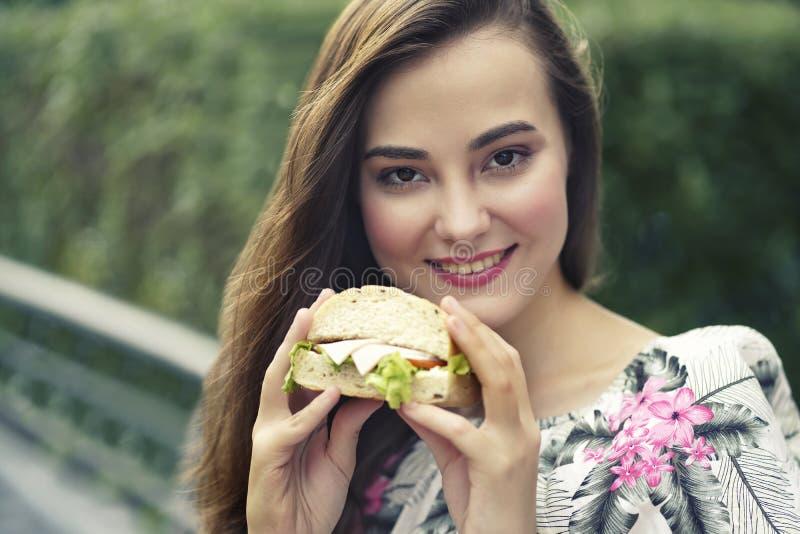 Die kaukasische Frau, die gesundes Sandwich hält für, genießen, das Mittagessen zu essen stockfotografie