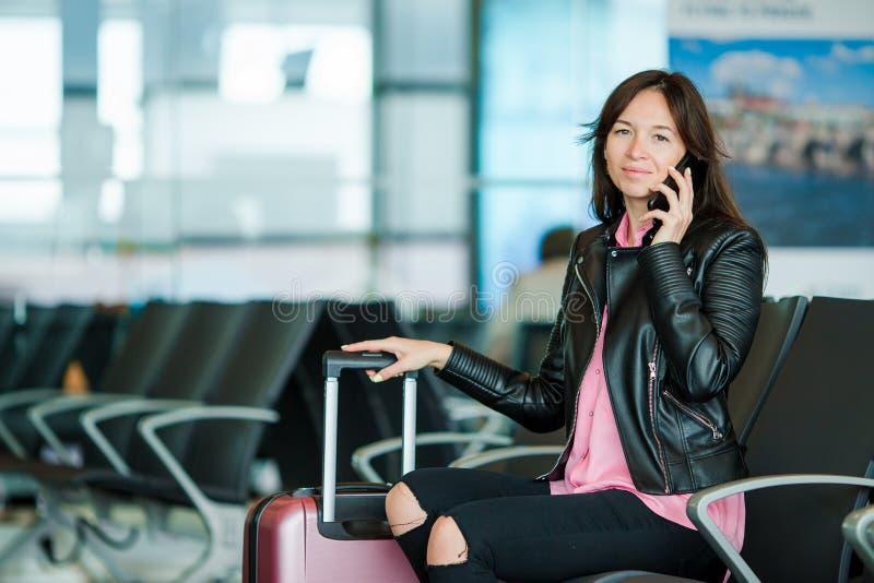Die kaukasische Frau, die Kamerawann betrachtet, spricht telefonisch im Warteraum lizenzfreie stockfotos