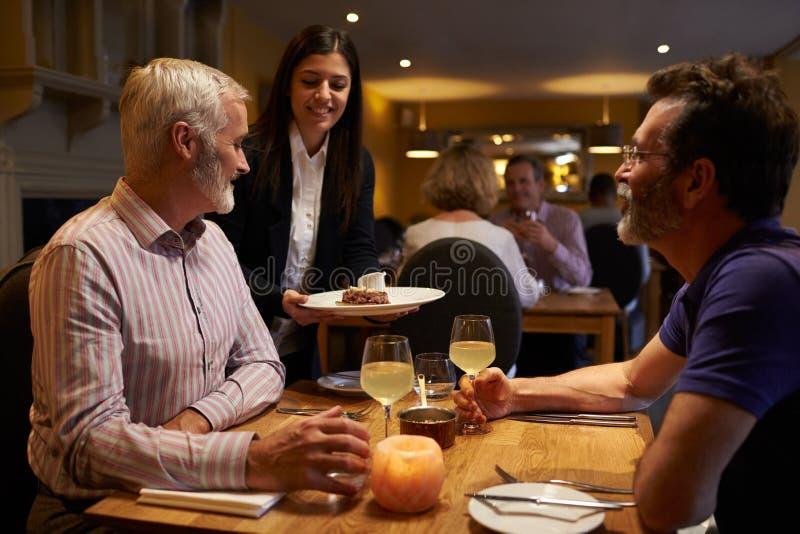 Die Kellnerin, die eine Mitte dient, alterte männliche Paare in einem Restaurant lizenzfreies stockbild