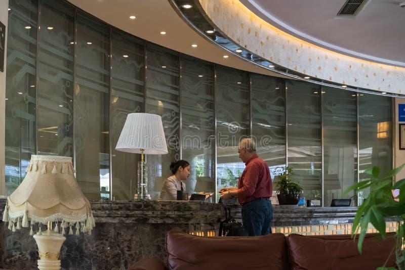Die Kellnerin empfing Gäste im Hotel lizenzfreie stockfotografie