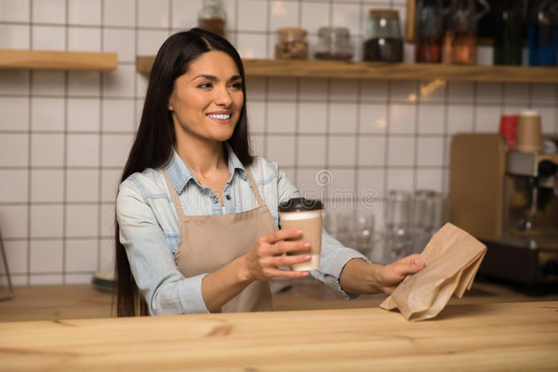 Die Kellnerin, die Kaffee zum Mitnehmen hält und nehmen Lebensmittel im Café weg stockfotografie