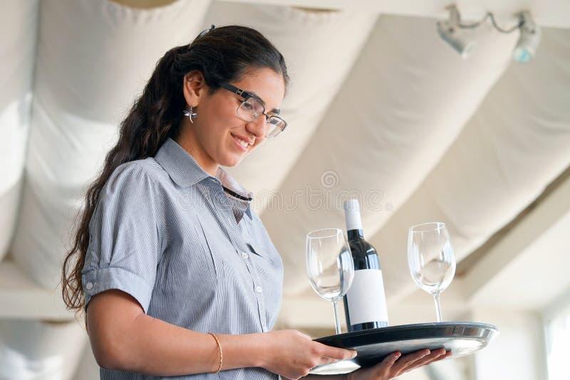 Die Kellnerin trägt eine Flasche Wein lizenzfreie stockbilder