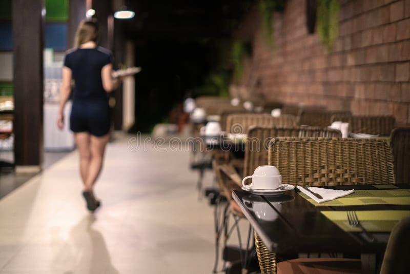 Die Kellnerin verlässt, das Café schließt Abend, Nacht, ist es Zeit, nach Hause zu gehen lizenzfreies stockbild