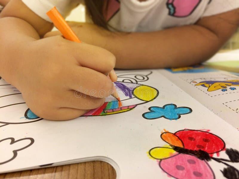 Die Kind-` s Hand malt auf Papier Es ist eine Fläche und hat ein f stockbild