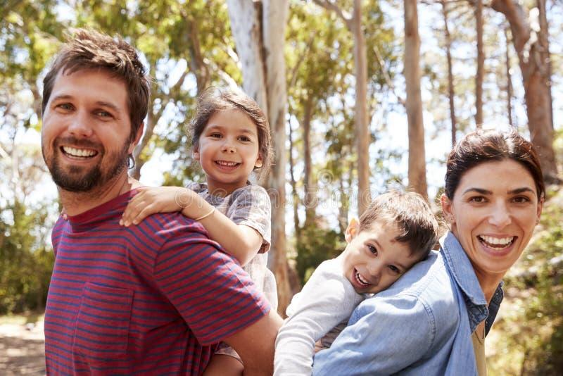Die Kinder, die auf Elternteil ` s Schultern auf Landschaft fahren, gehen lizenzfreie stockfotografie