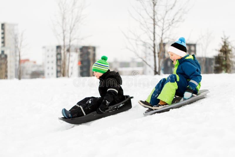 Die Kinder, die auf Schlitten schneien schieben unten, Hügel im Winter stockfoto