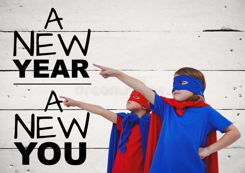 Die Kinder in den Superheldkostümen zeigend auf Gruß des neuen Jahres zitiert lizenzfreie stockfotos