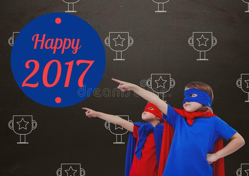 Die Kinder in den Superheldkostümen zeigend auf Gruß des neuen Jahres zitiert stockbild