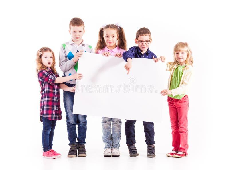 Die Kinder halten einen weißen freien Raum stockfotos