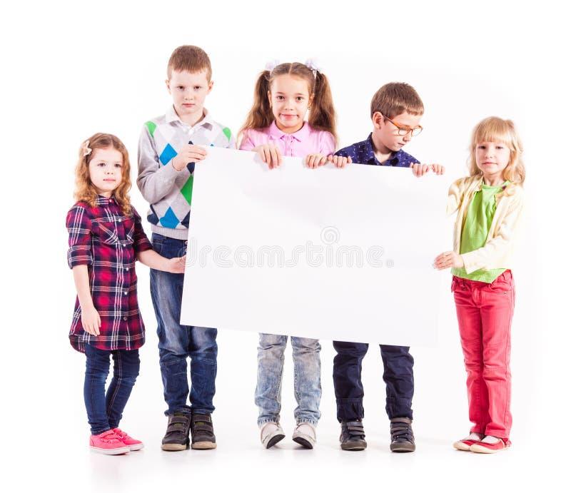 Die Kinder halten einen weißen freien Raum stockbild