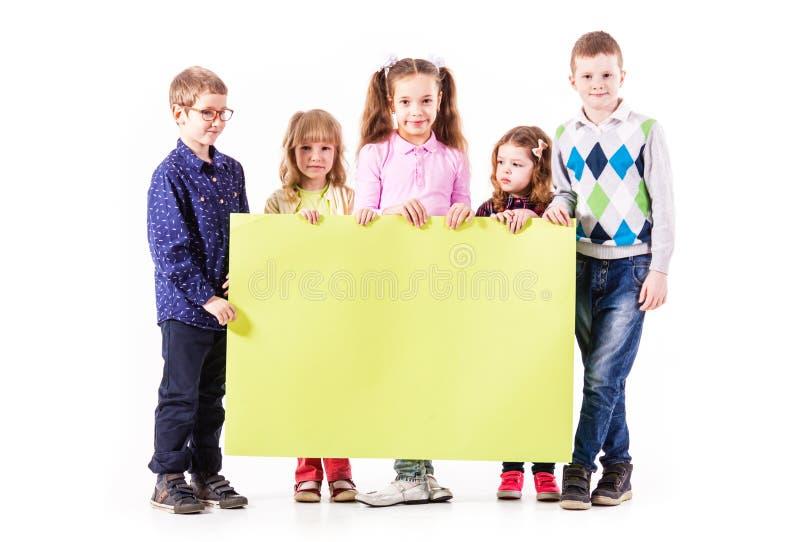 Die Kinder halten einen weißen freien Raum lizenzfreies stockfoto