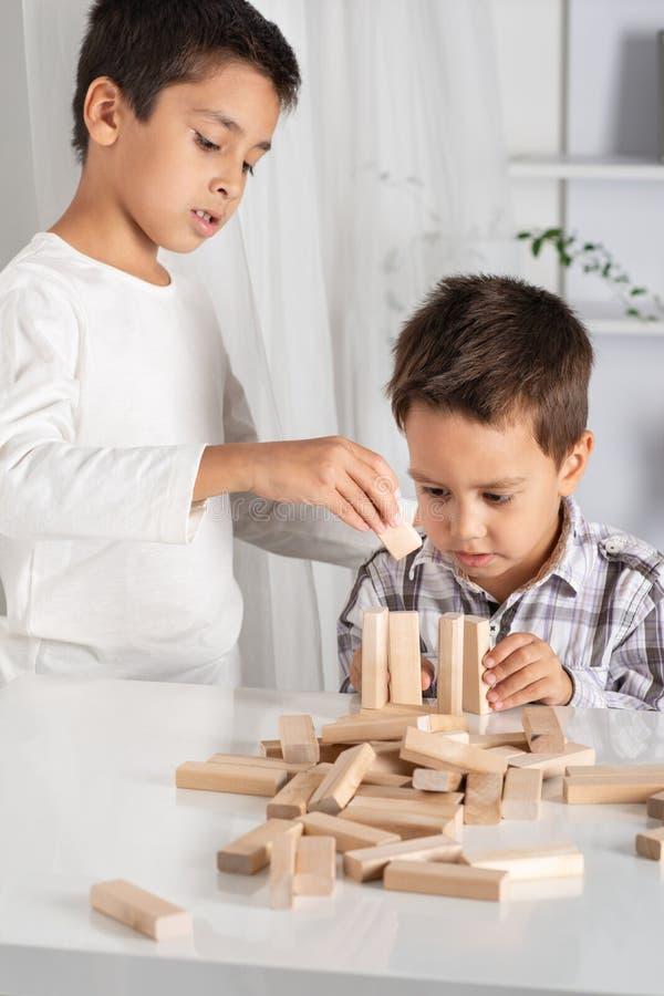 Die Kinder sitzen zuhause an einem Tisch und spielen enthusiastisch in einem w stockbild
