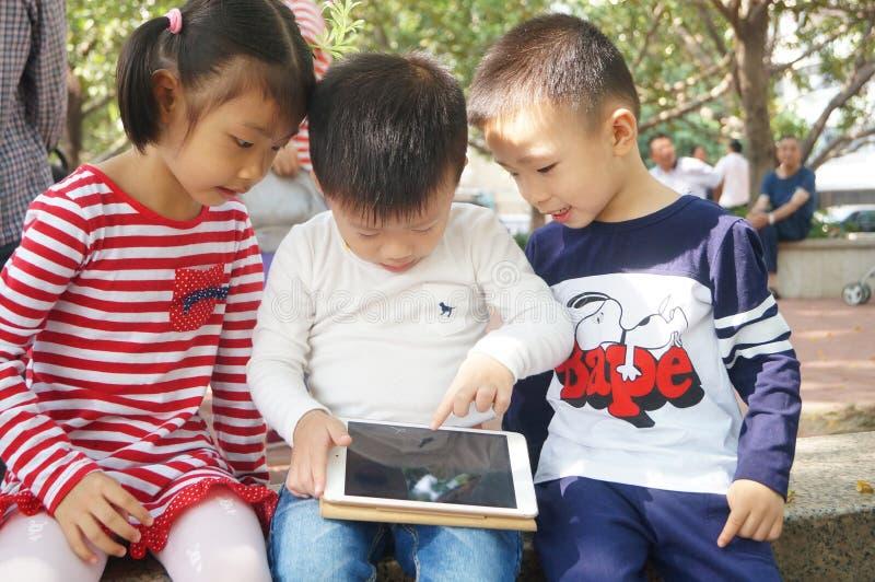 Die Kinder spielen in den Tabletten stockfoto
