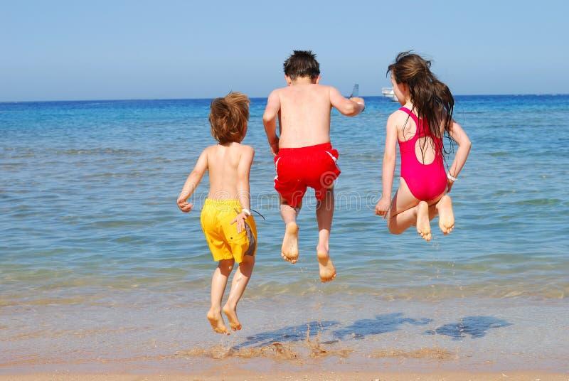 Die Kinder springend am Strand stockfotografie