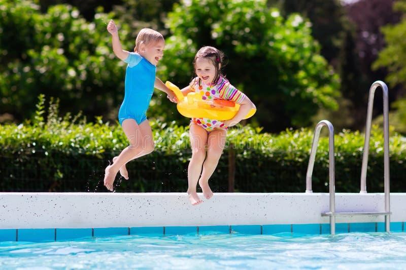 Die Kinder springend in Swimmingpool lizenzfreies stockbild