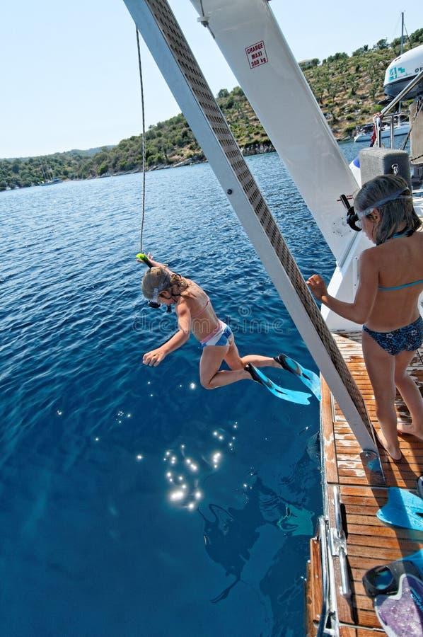 Die Kinder springend vom Boot lizenzfreie stockfotografie
