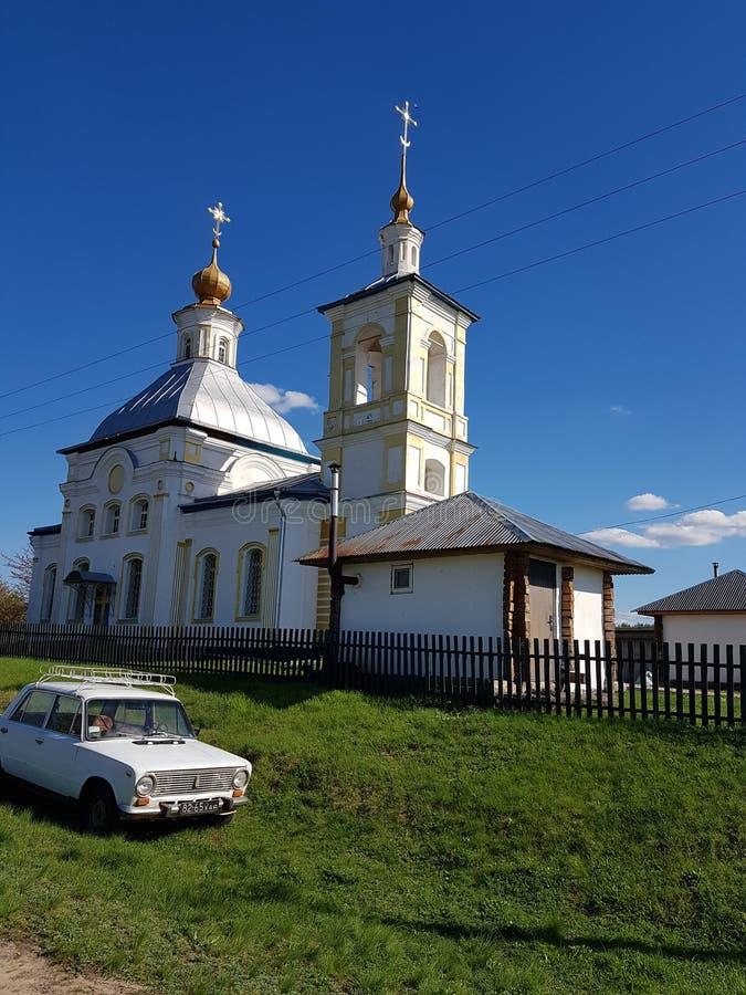 Die Kirche ist in der Farbe hinter einem Eisenzaun weiß Ein weißes Auto nahe der Kirche Grünes Gras Zwei Kreuze Gold in einem bla stockbilder