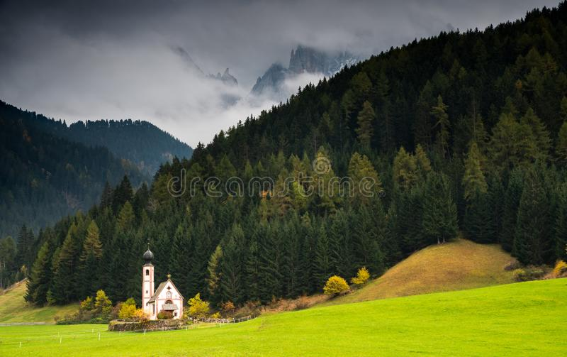 Die Kirche Saint John, Ranui, Chiesetta di san giovanni in Ranui Runes Südtirol Italien, umgeben von grüner Wiese, Wald stockfotos