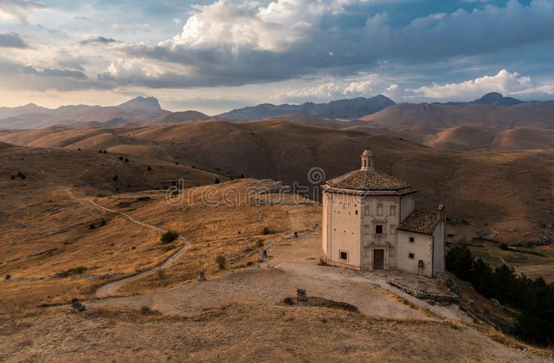 Die Kirche von Santa Maria-della Pietàin der Kleinstadt von Rocca Calascio während des Sonnenuntergangs lizenzfreie stockfotografie