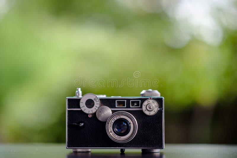 Die klassische Kamera, die auf dem Tisch gesetzt wird, schaut nicht teuer photogr stockbild
