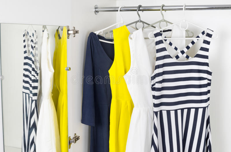 Die Kleider der modernen Modefrauen auf Aufhängern in einem weißen Schrank lizenzfreies stockbild
