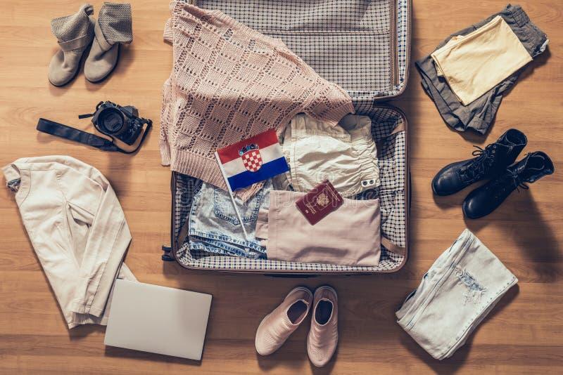 Die Kleidung der Frau, Laptop, Kamera, russischer Pass und Flagge von Kroatien liegend auf dem Parkettboden nahe und im offenen K stockfotos