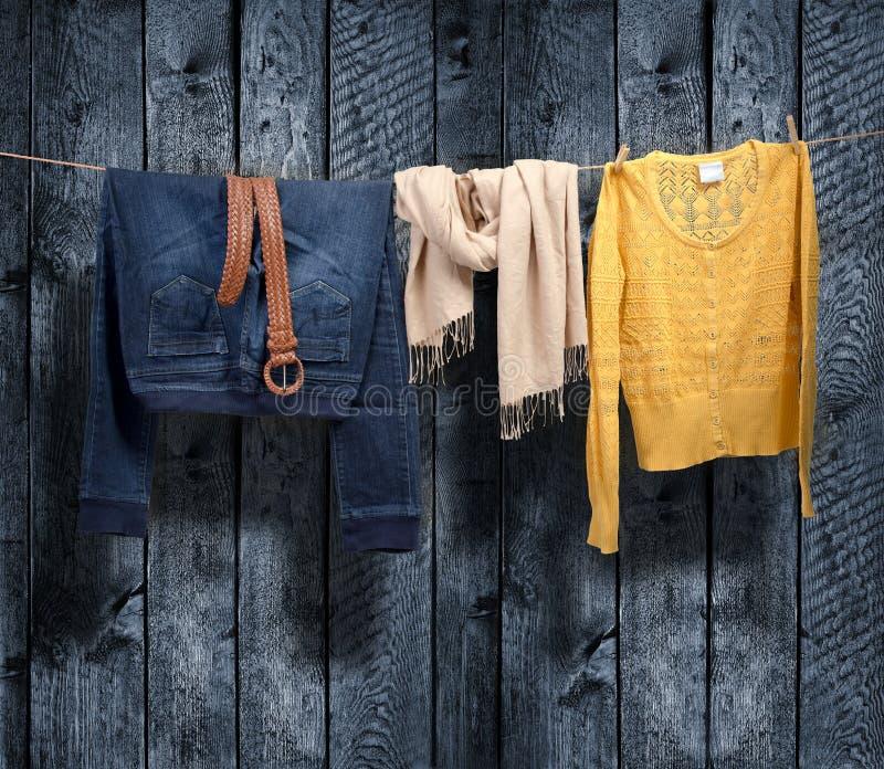Die Kleidung der Frauen auf einer Wäscheleine auf hölzernem Hintergrund stockfotos