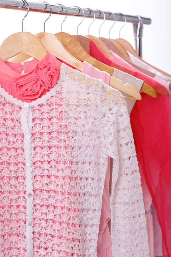 Die Kleidung der rosa Frauen auf Aufhängern auf Gestell auf weißem Hintergrund clos stockbilder