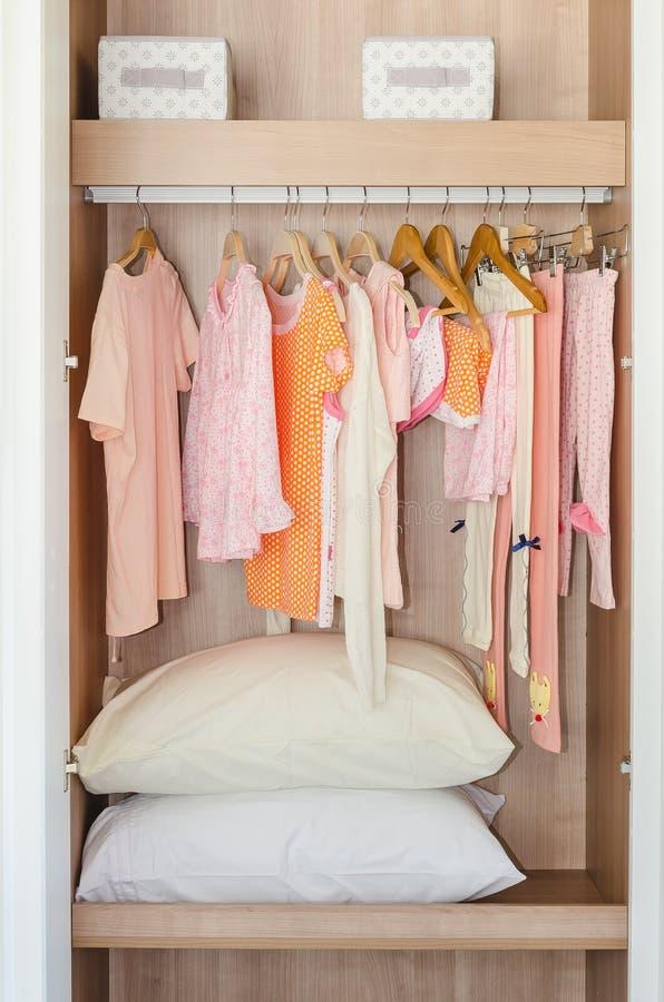 Die Kleidung des buntes Kindes, die an der Stange in der hölzernen Garderobe hängt lizenzfreie stockfotos