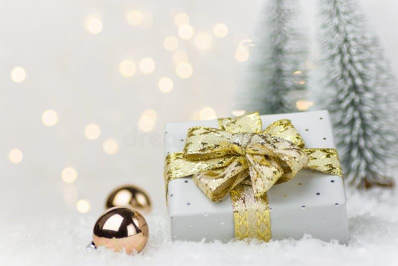 Die kleine elegante silberne Geschenkbox, die mit goldenem Bandbogenflitter im Winterszenenwald mit Tannenbäumen gebunden wird, s lizenzfreie stockfotografie