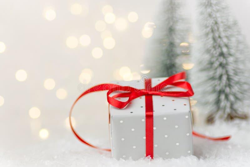 Die kleine elegante silberne Geschenkbox, die mit rotem Seidenband in der Winterszene im Wald mit Tannenbäumen gebunden wird, sch stockbilder