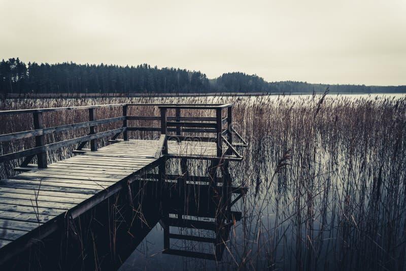 Die kleine Holzbrücke zum See im Herbst stockbilder
