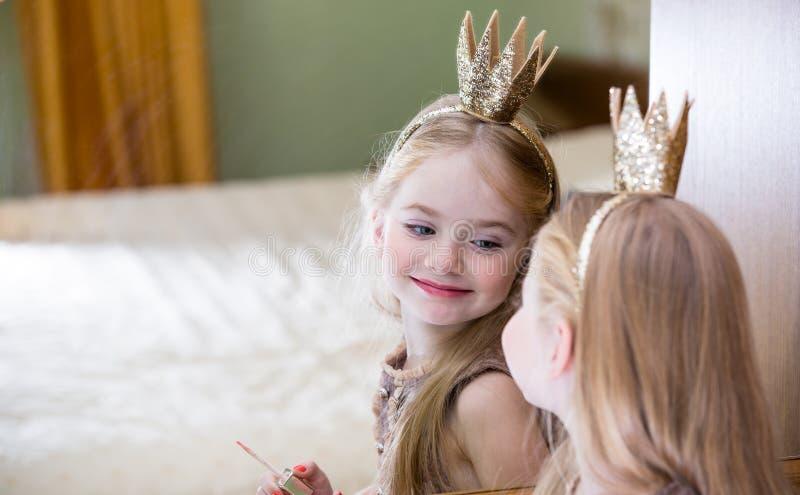 Die kleine Prinzessin schaut im Spiegel lizenzfreie stockbilder