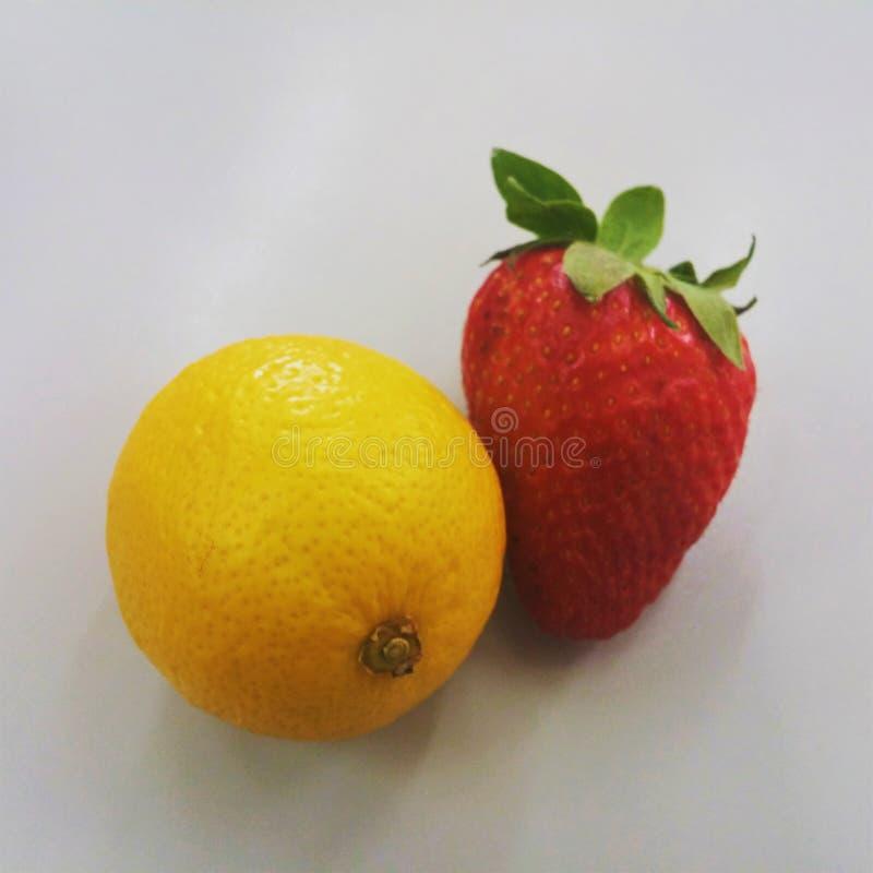 Die kleine Zitrone der selben Größe und die große Erdbeere auf neutralem Hintergrund lizenzfreie stockfotos