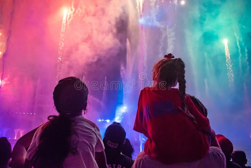 Die kleinen Mädchen, die Feuerwerke und Wasserstrahlen aufpassen, stellen bei Seaworld 2 dar lizenzfreies stockfoto