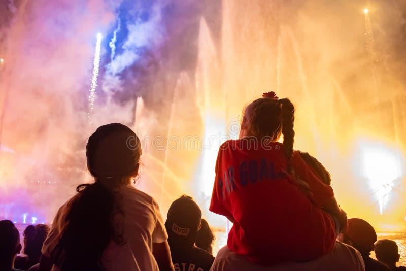 Die kleinen Mädchen, die Feuerwerke und Wasserstrahlen aufpassen, stellen bei Seaworld 1 dar stockfotos
